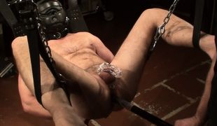 Sir lays Mr. Kristopher into the sling and removes the cold shackles from the prisoner's ankles