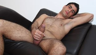 Hunky and hairy Sam arrives to wank the cum out of his uncut cock in his first video